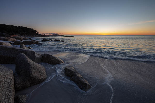 Orange glow on the horizon as the sun rises. Looking out across the water with waves rolling in and around coastal boulders. Bay of Fires, Tasmania, Australia